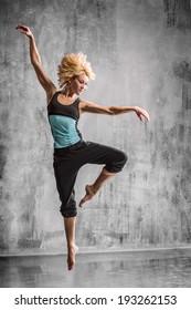 young beautiful dancer posing on studio background