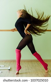 Young beautiful dancer posing in studio wit Ballet bar on tiptoe. Modern sexy brunette girl wears black tights practiced with handrail in the dance Long amazing hair. pink leggings.