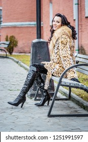 Young beautiful dark girl in black boots and spotted fur coat sitting on bench near red building