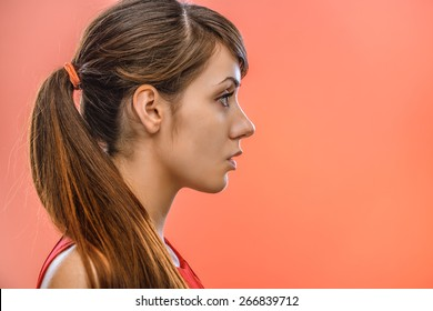 young beautiful dark-haired calm woman in profile, on red background