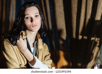 Young beautiful dark-haired woman sits on chairs near blackout curtains.