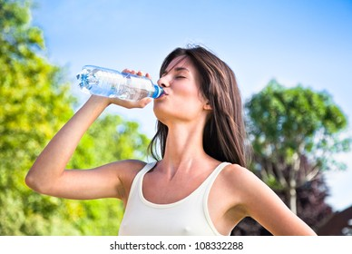 Young beautiful dark-haired woman wearing  t-shirt drinking water at summer green park.