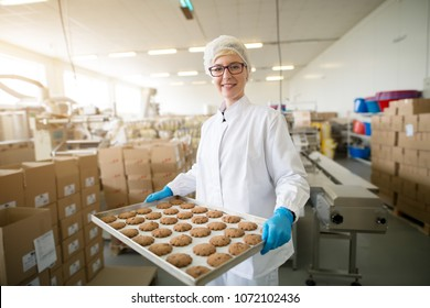Young beautiful dedicated female worker in sterile cloths carrying cookies on tin pan inside of healthy food production line.