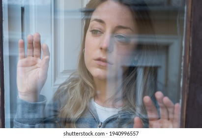 Young beautiful depressed unhappy caucasian woman looking worried and sad through the window at home. Feeling worthless and in pain. closeup. Depression and Mental Health concept