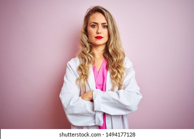 Young beautiful doctor woman standing over pink isolated background skeptic and nervous, disapproving expression on face with crossed arms. Negative person.