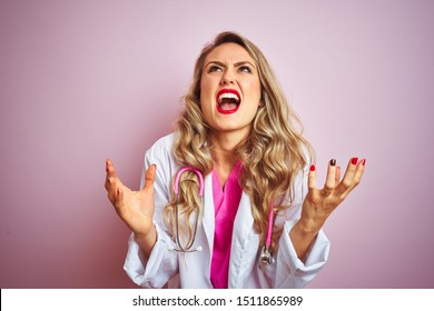 Young beautiful doctor woman using stethoscope over pink isolated background crazy and mad shouting and yelling with aggressive expression and arms raised. Frustration concept.