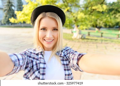 Young and beautiful. Elated pretty girl making selfie while having a walk around the city
