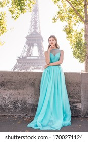 A young beautiful and elegant girl in a blue and green dress stands against the background of the Eiffel tower in Paris.