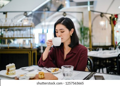 A young, beautiful and elegant Korean Asian woman sips tea from a white teacup as she enjoys a conversation with a close friend on the weekend over brunch and cake.
