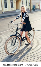 Young beautiful elegant vintage blonde woman posing on the street with her bicycle