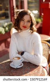 Young beautiful elegant woman in French style cafe wearing in white sweater with cup of coffee.