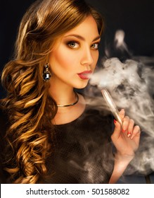 Young beautiful elegant woman in luxury dress smoking hookah over dark background. Glamour smoking.