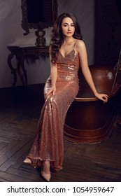 Young beautiful elegant woman wearing long evening shining dress sitting on bath in luxury dark interior. Pretty girl with makeup and long brunette wavy hair