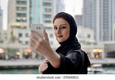 Young and beautiful Emirati woman taking selfie
