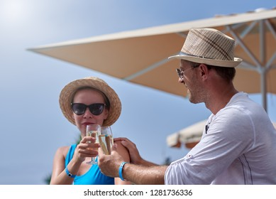 Young beautiful European family in sunhats is sitting at the city cafe. They are celebrating something, looking to each other, smiling and holding the glasses of champagne.