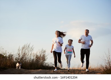 Young and beautiful family - father, mother and daughter are jogging with their dog outside the city on the village road on the setting sun