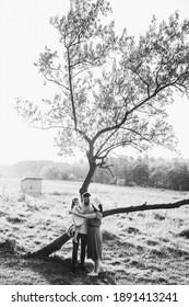 Young beautiful family near the tree. There is a cabin on the background. Black and white photo.