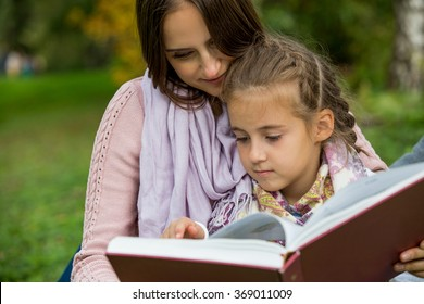 Young beautiful family sitting on the green grass in the park with big book. Reading fairy tale and smiling. Happy healthy family.