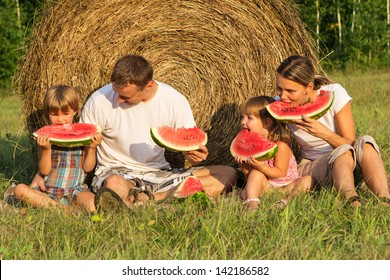 The young beautiful family in summer eats day water-melon outdoors