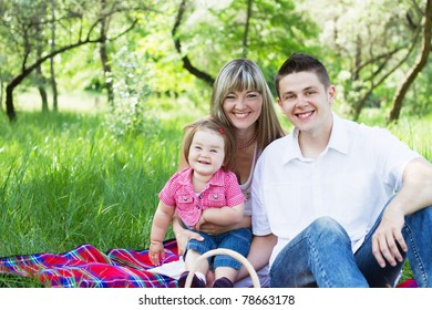 Young beautiful family of three on a picnic