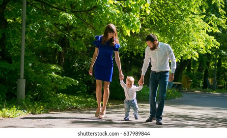 A young beautiful family is walking along the alley in the park.