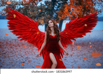 Young beautiful fantasy woman fallen angel stands near tree, orange falling leaves.  red suit costume artificial bird wings elegant dress. Wind magic whirls autumn foliage. Girl sexy goddess long hair