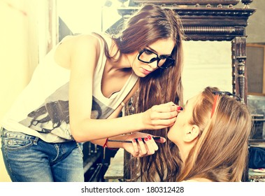 Young beautiful fashion girl applying make-up by make-up artist