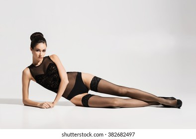 Young and beautiful fashion model posing in stockings and lingerie over white background