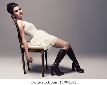 young beautiful fashion model sitting on a retro chair and looking at camera on gray background