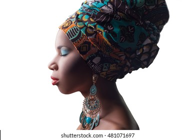 young beautiful fashion model with traditional african style with scarf, earrings and makeup and closed eyes isolated on white background.