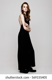 Young beautiful fashion model wearing black dress on grey background
