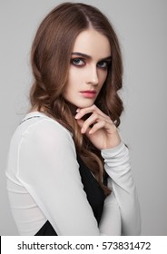 Young beautiful fashion model wearing black dress with white shirt on grey background