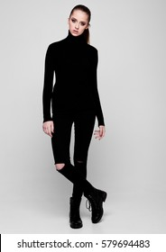 Young beautiful fashion model wearing black polo neck jumper and jeans on grey background