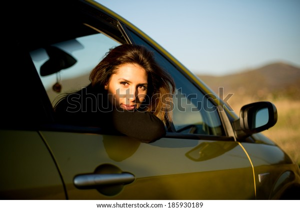 Young beautiful fashion woman seating in the car
