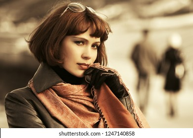 Young beautiful fashion woman walking on city street Stylish female model with bob hair wearing black leather coat and brown scarf