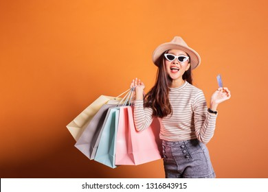 Young beautiful fashionable Asian woman holding shopping bags phone and credit card over orange background studio shot