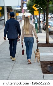Young beautiful fashionable couple a man and a woman in great shape are walking with a dog along the street of a modern city, enjoying the city landscapes and the urban lifestyle