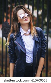 Young beautiful fashionable European girl, in a black leather jacket, stands next to a dark metal fence. Urban style of the street. Cold season. Fashionable portrait. sidewalk. Sunglasses, glasses