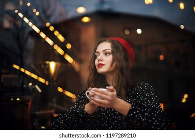 Young beautiful fashionable girl with red lips, long hair, wearing french style beret, polka dot blouse drinks coffee or tea in cafe. View through the window glass. Model looking up. Copy, empty space