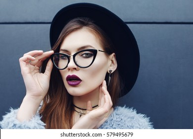 Young beautiful fashionable woman with long hair, trendy makeup. Model looking at camera, wearing stylish eyeglasses, fake fur coat, hat, accessories. Female fashion, beauty concept. Outdoor. Close up