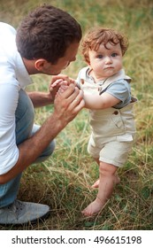 Young beautiful father and little toddler son against green grass. Happy father with her baby boy on a summer sunny day. Family walking on the meadow.