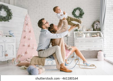 Young beautiful father and mother with baby in christmas decor studio having fun