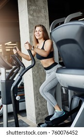 Young beautiful female athlete using elliptical cross trainer to warm up her muscles. Running in gym on a sunny winter morning.