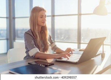 Young beautiful female copywriter typing texts and blogs in spacious light office, her workplace, using pc keyboard. Busy woman working.