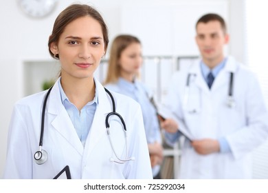 Young beautiful female doctor smiling  on the background with patient  in hospital