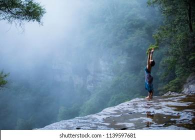 Young beautiful female doing yoga pose above Blue Mountains, Sydney Australia