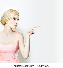 Young beautiful female in elegant fashion pointing at blank copyspace to right in a studio advertising conceptual