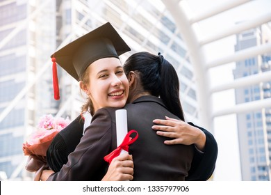 Young beautiful female graduate hugging her mother at graduation ceremony at home town, city background. Education concept.