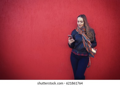 Young beautiful female hipster reading news and chatting with friends on mobile phone using 4G free connection outdoors while standing on copy space background. Area for your advertising content
