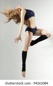Young and beautiful female jumping high over grey background